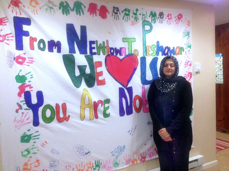 """Kanwal Sakhi stands by the poster she is taking to Peshawar Pakistan Tuesday telling the families there """"U are not alone."""" Photo: Susan Tuz/ Staff, Susan Tuz / The News-Times"""