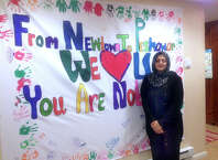 """Kanwal Sakhi stands by the poster she is taking to Peshawar Pakistan Tuesday telling the families there """"U are not alone."""""""