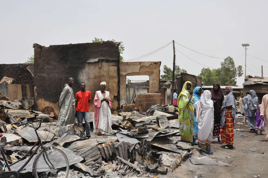"FILE- In this Sunday, May 11, 2014 file photo, people stand outside burnt houses following an attack by Islamic militants in Gambaru, Nigeria. Thousands of members of Nigeria's home-grown Islamic extremist Boko Haram group strike across the border in Cameroon, with coordinated attacks on border towns, a troop convoy and a major barracks. Further north, Boko Haram employs recruits from Chad to enforce its control in northeastern Nigerian towns and cities. In Niger, the government has declared a ""humanitarian crisis"" and appealed for international aid to help tens of thousands of Nigerian refugees driven from their homes by the insurgency. (AP Photo/Jossy Ola, File) Photo: Jossy Ola / Associated Press / AP"