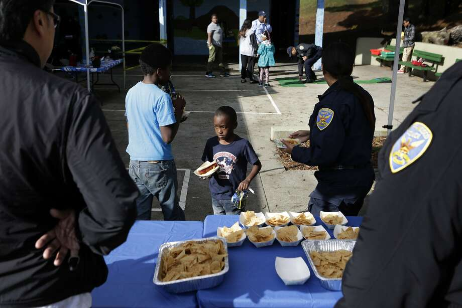 Cassanova Holmon (6) receives a hot dog from police officers during a kickoff event for the annual Operation Dream Toy Drive at Herz Park in San Francisco's Visitacion Valley on Saturday, December 13, 2014. The toy drive is sponsored in part by the San Francisco Police Department. It marks its 20th anniversary this year. Photo: Terray Sylvester, The Chronicle