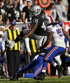 Oakland Raiders' Marcel Reese hurdles Buffalo Bills' Corey Graham in 2nd quarter during NFL game at O.co Coliseum in Oakland, Calif., on Sunday, December 21, 2014.