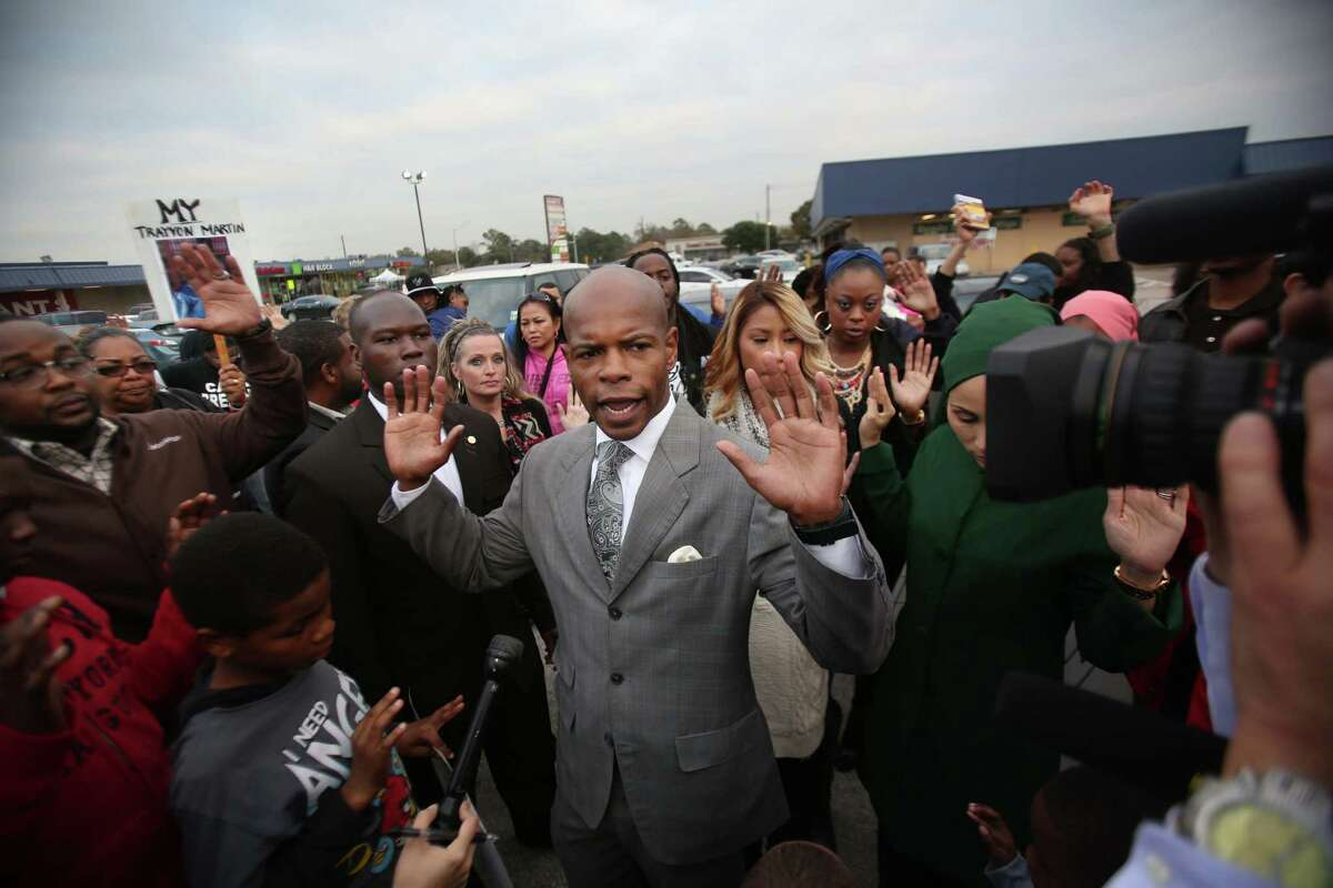 """""""Don't Shoot"""" says Activist Deric Muhammad while holding up his hands along with supporters during the candlelight vigil for Jordan Baker in the parking lot where he was shot by police on Sunday, Dec. 21, 2014, in Houston."""