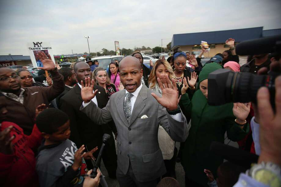 """Don't Shoot"" says Activist Deric Muhammad while holding up his hands along with supporters during the candlelight vigil for Jordan Baker in the parking lot where he was shot by police on Sunday, Dec. 21, 2014, in Houston. Photo: Mayra Beltran, Houston Chronicle / © 2014 Houston Chronicle"