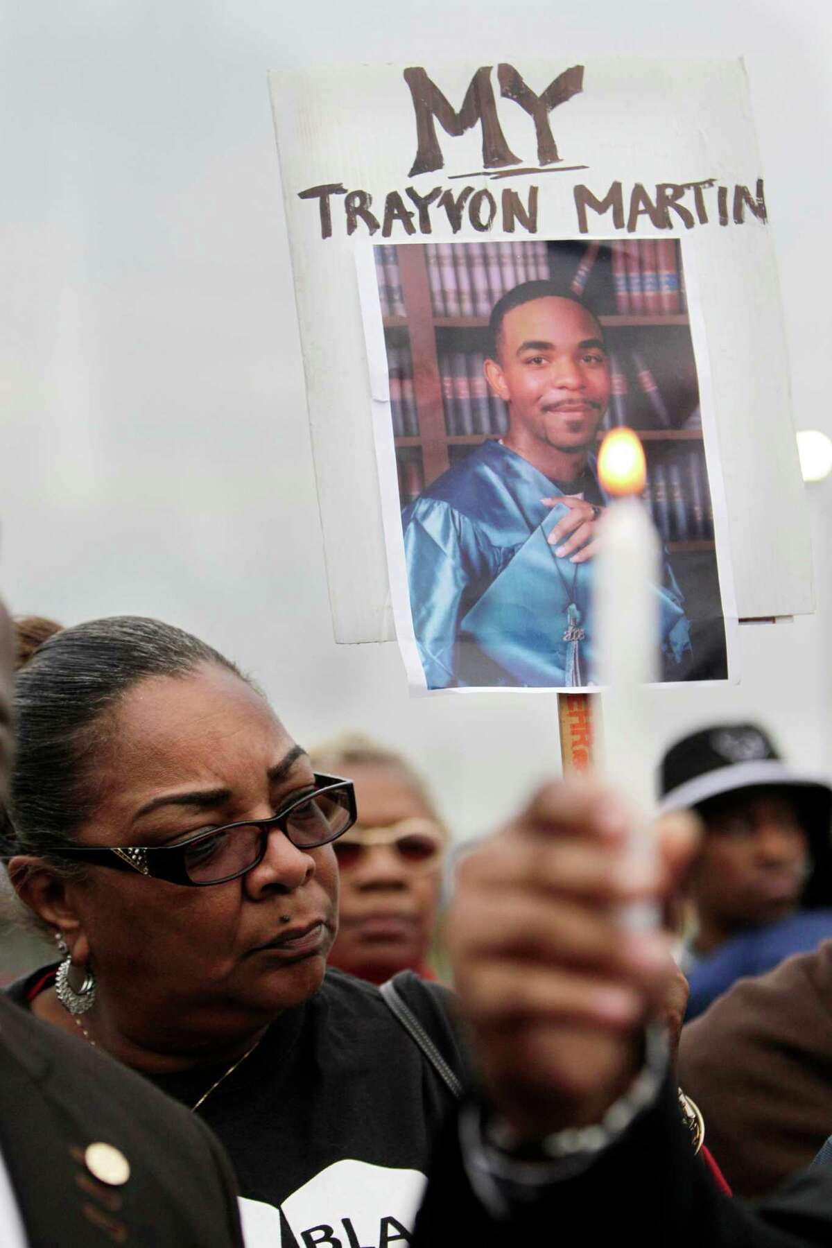 Kathy Blueford-Daniels, holds a photo of her murdered son, while she attends a vigil for Jordan Baker in the parking lot where he was shot by police on Sunday, Dec. 21, 2014, in Houston.