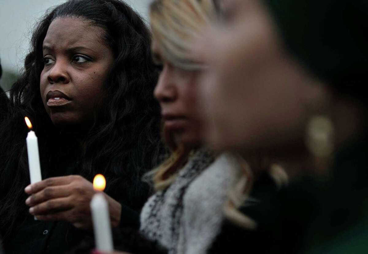 Janet Baker, mother of Jordan Baker, holds a candlelight vigil for son Jordan Baker in the parking lot where he was shot by police on Sunday, Dec. 21, 2014, in Houston.