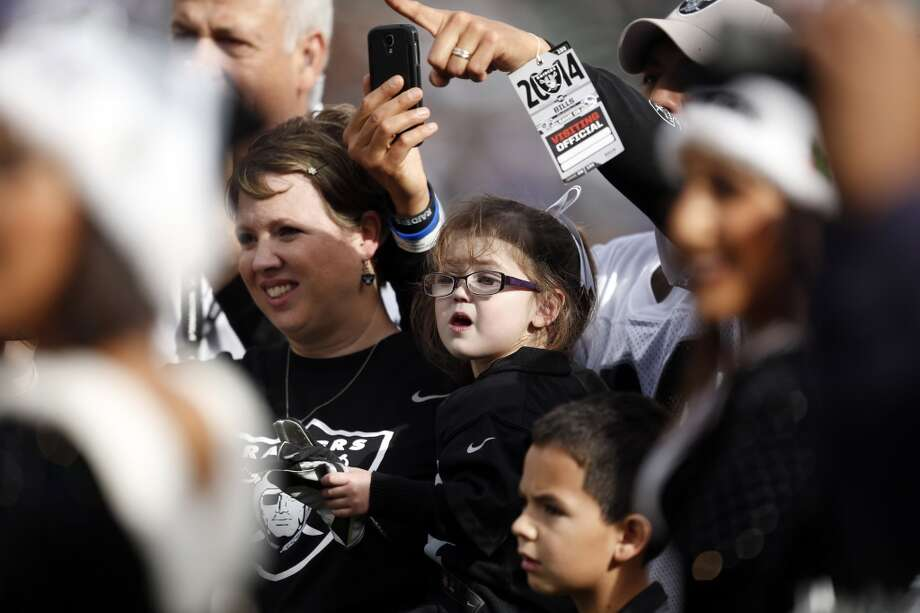 Amy Urrea holds her daughter Ava, 4, during pre-game introductions before Oakland Raiders play Buffalo Bills during NFL game at O.co Coliseum in Oakland, Calif., on Sunday, December 21, 2014. Raiders' Menelik Watson has donated his game check to the Urrea family to help defray Ava's medical costs. Photo: Scott Strazzante, The Chronicle