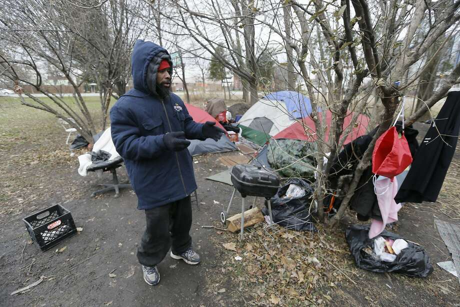 In a photo from Wednesday, Dec. 17, 2014, Charles Floyd Jones picks up trash at the tent city on the eastern edge of downtown Detroit. Jones can only hope that the city's good fortune trickles down to him and the 10 other residents of a tent city that's sprouted in the shadow of a resurgent downtown where rental occupancy is close to full and retail square-footage fetches top dollar. Jones and others in this makeshift community of seven tents say they have nowhere else to go. Photo: Carlos Osorio, Associated Press