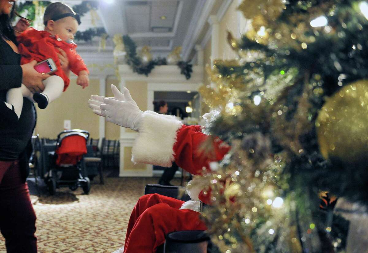 Emily Roth, eight months old, from Niskayuna, is handed over to Santa to get her photo taken during the Brunch with Santa event at Angelo's Tavolo at Glen Sanders Mansion on Sunday, Dec. 21, 2014, in Scotia, N.Y. Angelo's Tavolo hosted the brunch, which it has every Sunday, making this one special with the addition of Santa. (Paul Buckowski / Times Union)