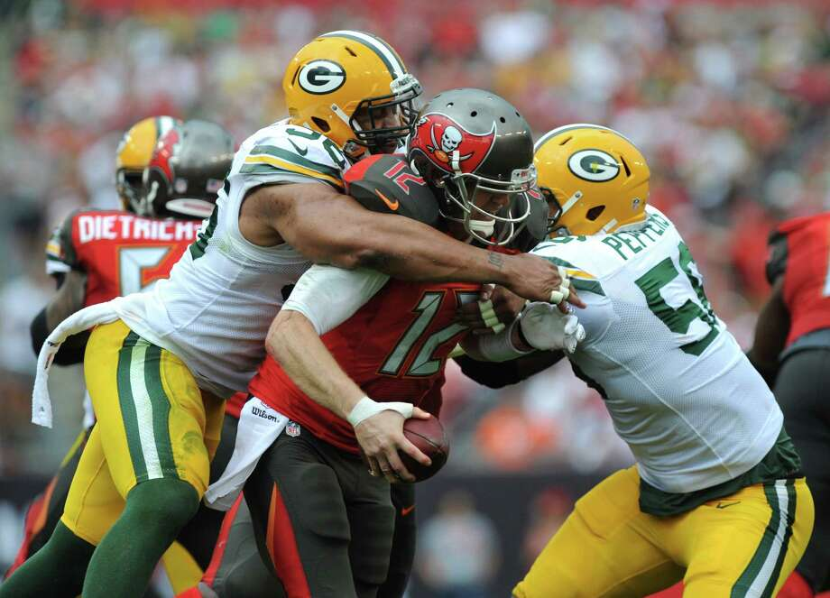 TAMPA, FL - DECEMBER 21: Defensive end Mike Neal #96 of the Green Bay Packers and outside linebacker outside linebacker Julius Peppers #56 of the Green Bay Packers sack quarterback Josh McCown #12 of the Tampa Bay Buccaneers in the third quarter at Raymond James Stadium on December 21, 2014 in Tampa, Florida. (Photo by Cliff McBride/Getty Images) ORG XMIT: 507883141 Photo: Cliff McBride / 2014 Getty Images