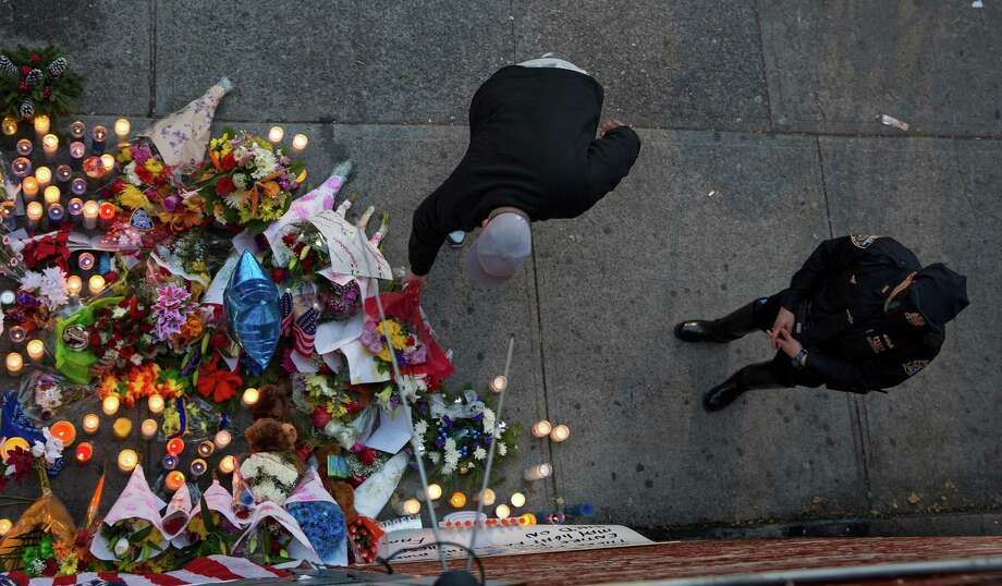 An NYPD officer stands by a memorial Sunday, Dec. 21, 2014, honoring two New York Police Department officers who were shot while sitting inside a patrol car nearby the previous day. The armed man shot into the patrol car, killing them both. The assailant then went into a nearby subway station and committed suicide, police said. (AP Photo/Craig Ruttle) ORG XMIT: NYCR103 Photo: Craig Ruttle / FR61802 AP