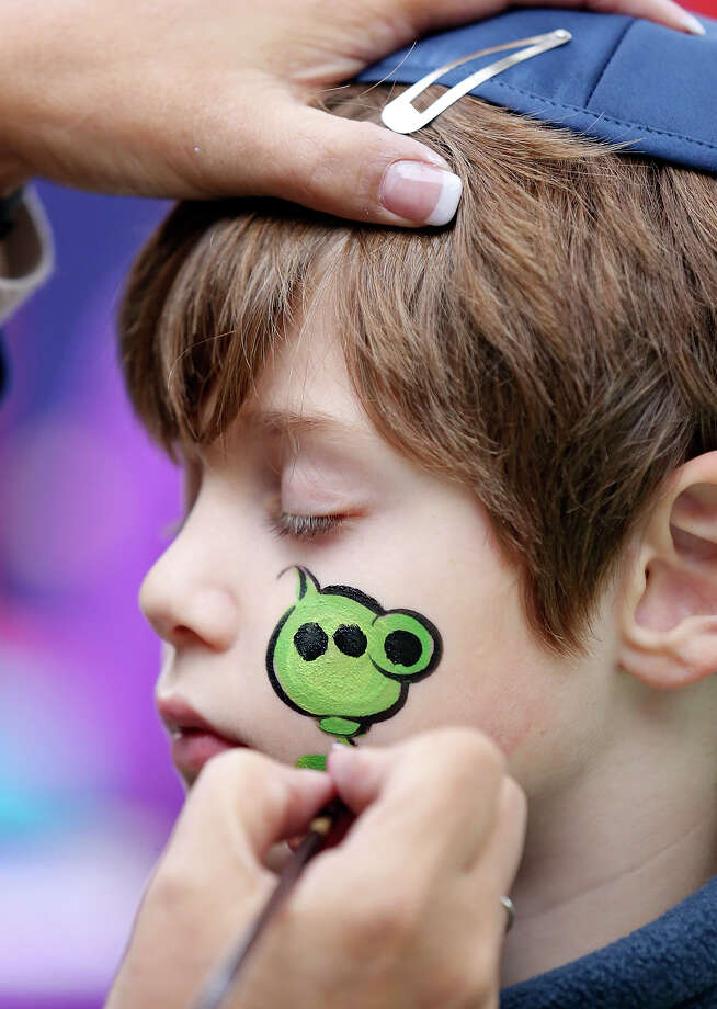"Jonas Pfrenger, 7, gets a ""Peashooter"" painted on his face by artist Liz Alaniz while attending the Chabad Lubavitch of South Texas' 17th annual Chanukah on the River Sunday Dec. 21, 2014 at Maverick Plaza in La Villita. Activities included a Menorah lighting, arts and crafts, Chanukah barge parade, food, live music, and a play area. Photo: Edward A. Ornelas, Staff / San Antonio Express-News / © 2014 San Antonio Express-News"