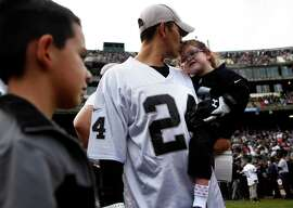 Ava Urrea, who has a heart condition, is held by Edward, her dad. The Urreas were given a game check by Menelik Watson.