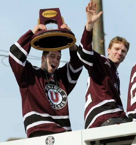 Union's Theo DiPauli, left, hoists the NCAA Hockey Championship trophy as he rides a fire truck with Mat Bodie, right, and teammates during a parade to honor them on Thursday, April 17, 2014, in Schenectady, N.Y. (Cindy Schultz / Times Union) Photo: Cindy Schultz / 00026500A