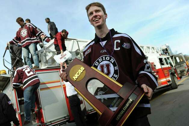 Union's Mat Bodie, center, carries the team's NCAA Hockey Championship trophy as they disembark from a fire truck the team rode in a parade during a celebration to mark the team's achievement on Thursday, April 17, 2014, at City Hall in Schenectady, N.Y. (Cindy Schultz / Times Union) Photo: Cindy Schultz / 00026500A