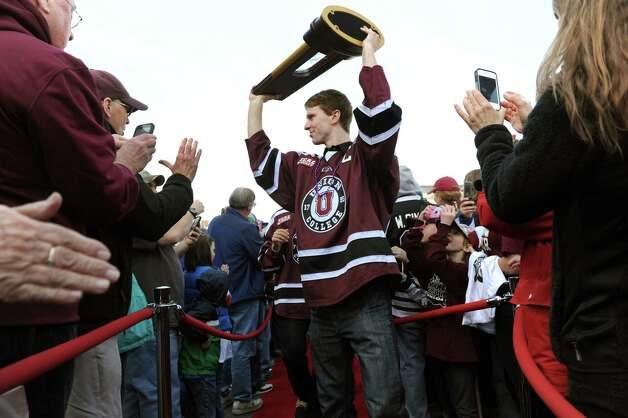 Union's Mat Bodie, center, carries the team's NCAA Hockey Championship trophy through a sea of fans during a celebration to mark the team's achievement on Thursday, April 17, 2014, at City Hall in Schenectady, N.Y. (Cindy Schultz / Times Union) Photo: Cindy Schultz / 00026500A