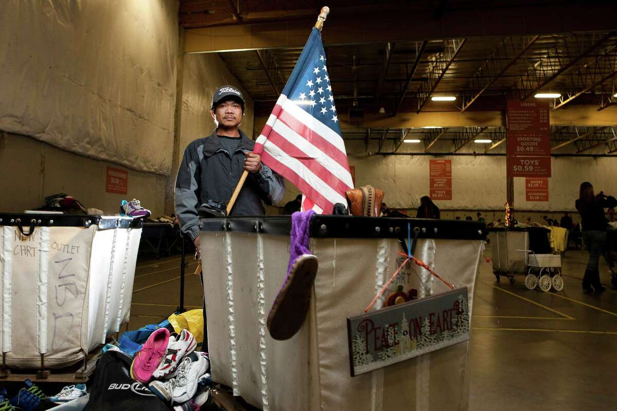 Marlon Baluca, 35, finds an American flag while shopping for shoes at the Seattle Goodwill Outlet.