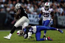 Buffalo's Ron Brooks struggles to tackle Raiders running back Latavius Murray, who ran for a game-high 86 yards.