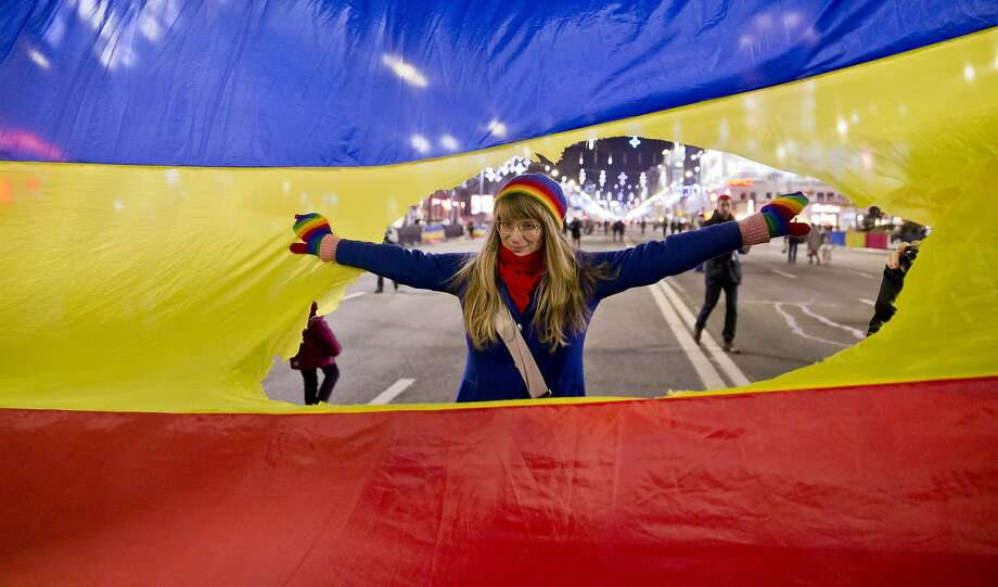 A girl poses for a picture inside a large symbolic revolution Romania flag with the communist crest cut out during a reenactment of the 1989 uprising in Bucharest, Romania, Sunday, Dec. 21, 2014.  The anti-communist uprising, which left more than one thousand dead, and ended the rule of dictator Nicolae Ceausescu, who was executed, started 25 years ago in the western Romanian town of Timisoara on Dec. 16, 1989 and continued in Bucharest, Romania's capital from Dec. 21, 1989.(AP Photo/Vadim Ghirda) Photo: Vadim Ghirda, Associated Press