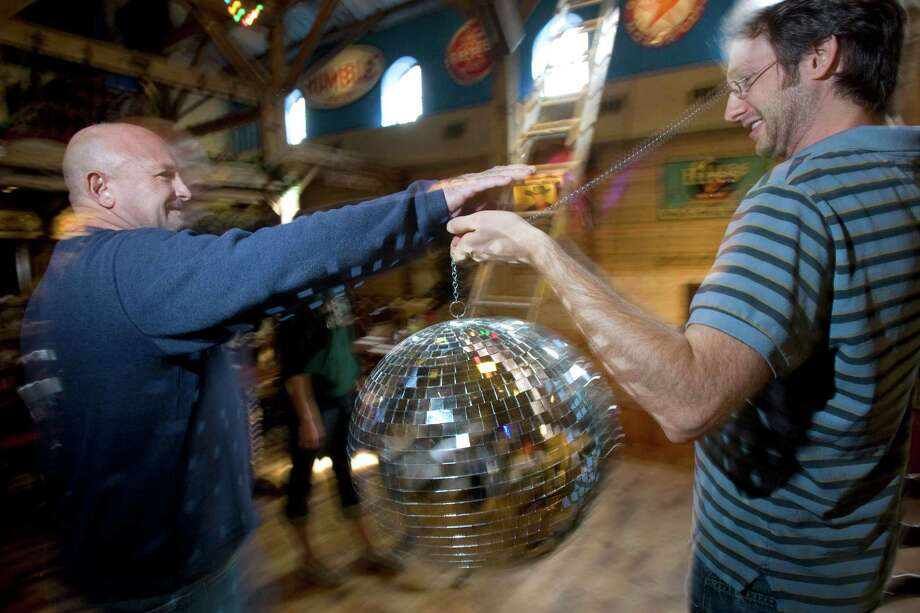 Stephen Said, left, and Brad Said co-owners of Dosey Doe, prepared for a past New Year's Eve party  by setting up a disco ball. Photo: Johnny Hanson, Staff / Houston Chronicle