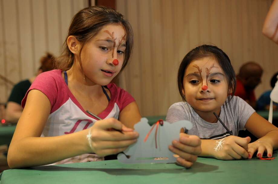 Chelsea Lira, 10, left, a fifth-grader at Cedar Brook Elementary, shows Meleney Soria, 7, a Cedar Brook Elementary second-grader, her homemade Christmas ornament at the crafts station at the Spring Branch FFA Santa's Farm. Photo: Jerry Baker, Freelance