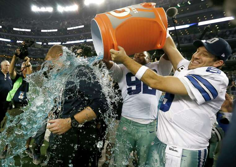 Jason Garrett is doused by Jeremy Mincey and Tony Romo after their 42-7 win over the Indianapolis Co