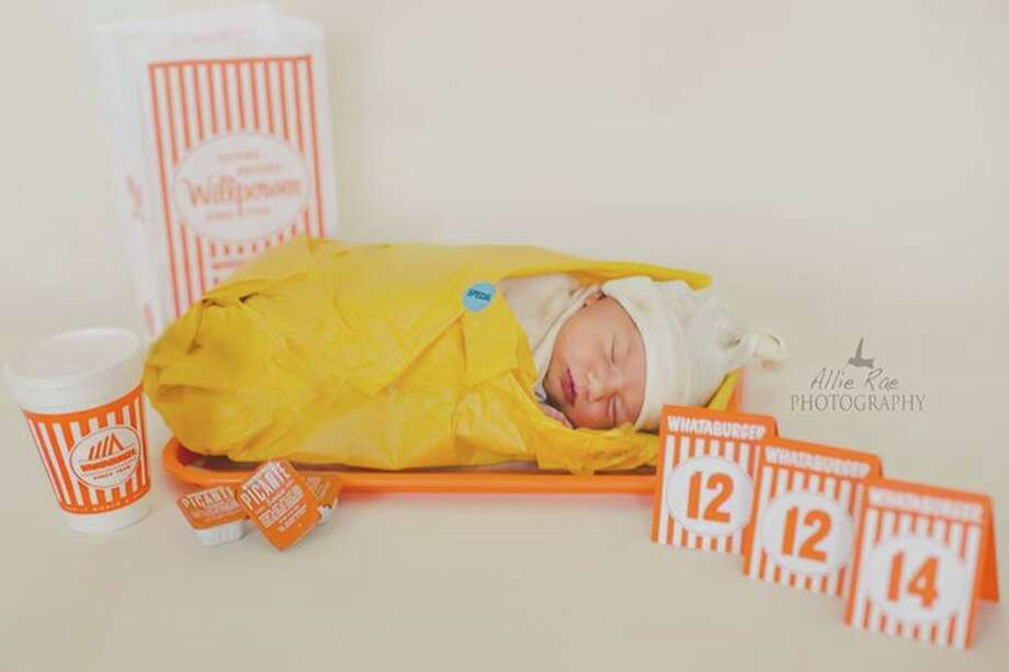 One Texas couple showed their passion for Whataburger by transforming their newborn into a taquito. The baby, Basil Riddle, is swaddled in a yellow taquito wrapper and laying on an orange tray, surrounded with picante sauce and the iconic table tents with numbers of the baby's birthday. Photo: Courtesy/Allie Rae Photography