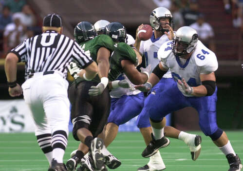 Eastern Illinois quarterback Tony Romo, center, throws from the pocket against Hawaii during the first quarter at Aloha Stadium in Honolulu, Saturday, Aug. 31, 2002. At right is Eastern Illinois's Scott Sholl (64). Photo: RONEN ZILBERMAN, AP Photo/Ronen Zilberman / AP2002