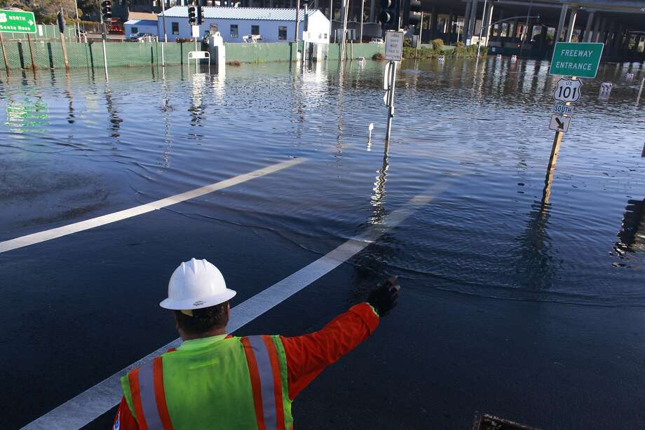 "Cal Trans maintenance worker Doc Ramsey directs traffic after a record high tide known as a ""king tide"" floods roads near the Manzanita Park And Ride on Wednesday Dec. 12, 2012 in Mill Valley, Calif. Photo: Mike Kepka, The Chronicle"