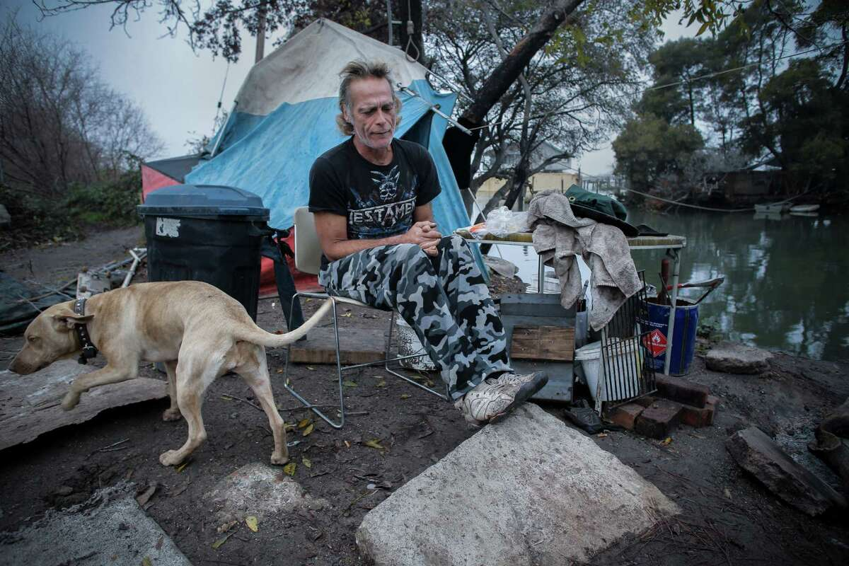 """Greg Goss and his dog """"Mom"""" at the homeless encampment where he lives on the edge of the San Joaquin river in Antioch, Calif. as seen on Friday Dec. 5, 2014."""