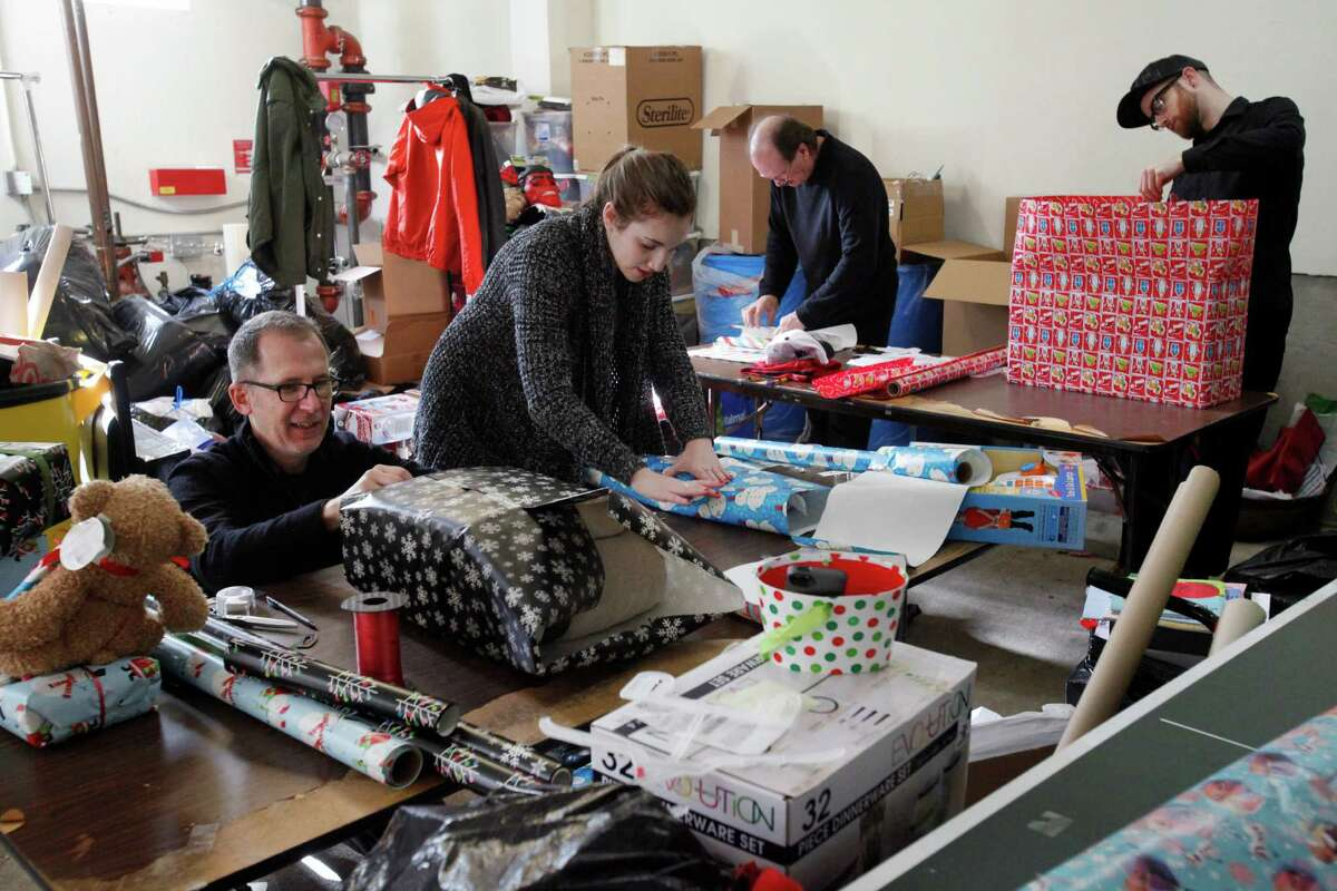 Members of Bloomingdale's visual merchandising team - Jay Young (left), Rachel Goldman, John Gilligan and William Curry - wrap gifts for homeless families last Tuesday at the Hamilton Family Center in S.F.