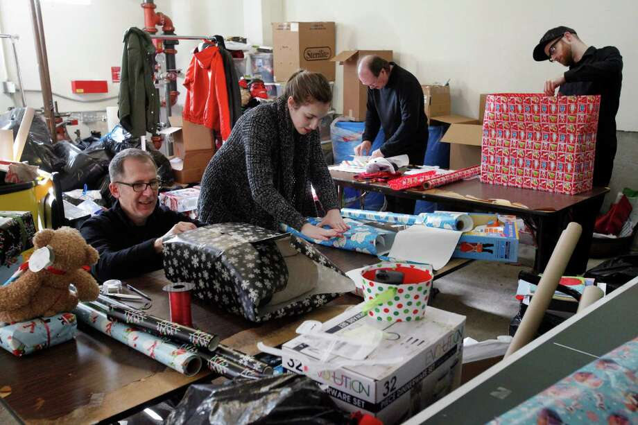 Members of Bloomingdale's visual merchandising team — Jay Young (left), Rachel Goldman, John Gilligan and William Curry — wrap gifts for homeless families last Tuesday at the Hamilton Family Center in S.F. Photo: Leah Millis / The Chronicle / ONLINE_YES