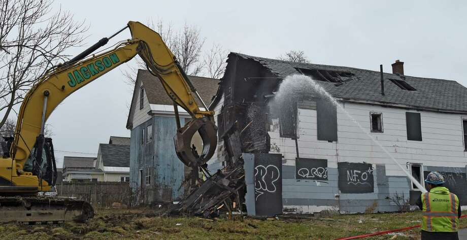 Mayor Gary McCarthy kicked off the start of demolition of 1150 Cutler St. Monday morning, Dec. 22, 2014, in Schenectady, N.Y. The home was damaged beyond repair by fire and was demolished as part of the $7 million initiative to rebuild Schenectady.   (Skip Dickstein/Times Union) Photo: SKIP DICKSTEIN / 00029960A