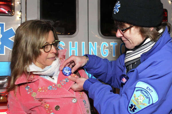 Ambulance EMT pins a flashing button on Kristy Kunhardt during Washington's traditional Holiday in the Depot, Dec. 12, 2014