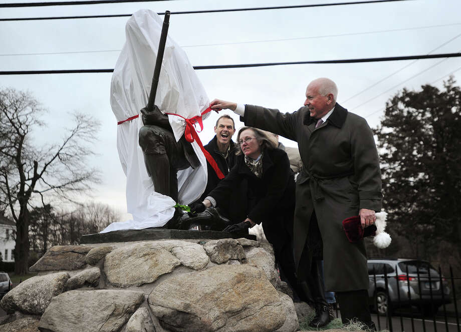 From left; Restorer Francis Miller, of ConservArt, LLC in Hamden, Ginger and Jim Donaher, of Gault, Co., and Westport First Selectman Jim Marpe unveil the newly-restored Minuteman statue on Compo Road in Westport, Conn. on Monday, December 22, 2014. The majority of restoration work done was to rebuild and repoint the surounding stone wall and statue pedestal, as well as the cast iron fence that sits above the circular wall. Photo: Brian A. Pounds / Connecticut Post