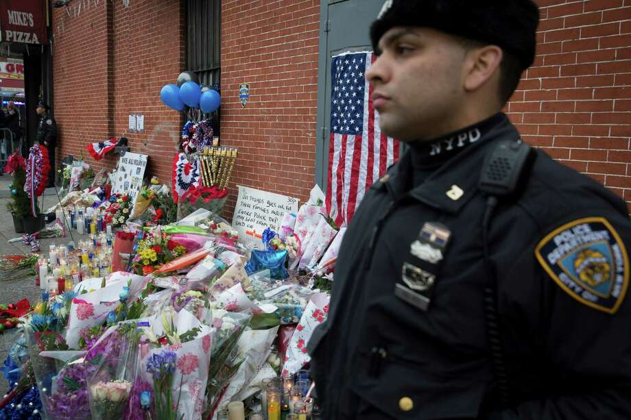 A NYPD officer stands guard beside a makeshift memorial Monday, near the site where two officers were killed. Photo: John Minchillo / Associated Press / FR170537 AP