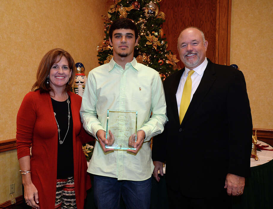 Football offensive and defensive MVP Sage Seay of Nederland poses with Howell Furniture's Shawn Hanley and Mark Adkins, Publisher of The Beaumont Enterprise, at the Super Gold award ceremony for the area's volleyball and football star athletes at the Elegante Monday night. Photo taken Monday, December 15, 2014 Kim Brent/The Enterprise Photo: Kim Brent / Beaumont Enterprise