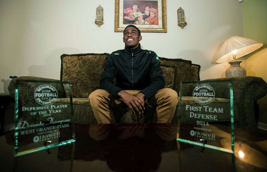 Deionte Thompson poses with his Super Gold football awards at his home Tuesday evening. Photo taken Tuesday 12/16/14 Jake Daniels/The Enterprise Photo: Jake Daniels / ©2014 The Beaumont Enterprise/Jake Daniels