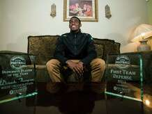 Deionte Thompson poses with his Super Gold football awards at his home Tuesday evening. Photo taken Tuesday 12/16/14 Jake Daniels/The Enterprise