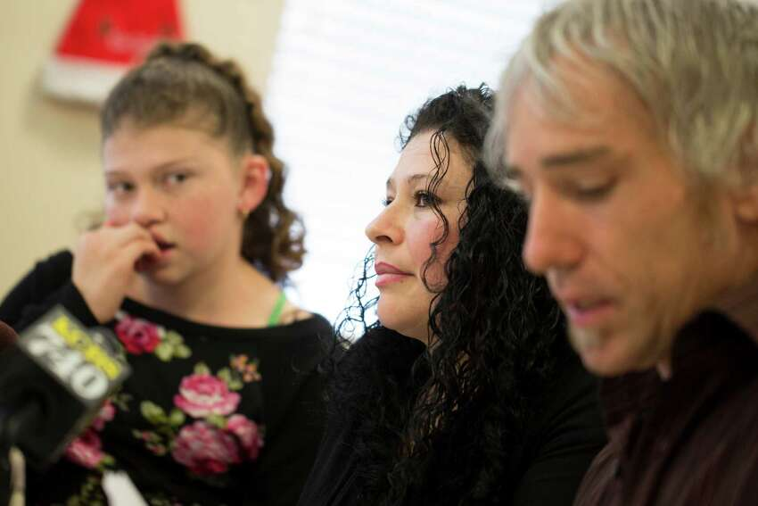 Maricela Perez, center, wife of Pedro Perez, a San Leandro man who fell from an 11-story building in San Francisco while window washing, speaks about her husband's recovery with her daughter Gaby Perez, 11, left, and Colin O'Leary, right, a Service Employees International Union organizer, at the SEIU United Service Workers West office in Oakland, Calif. on Monday, December 22, 2014.
