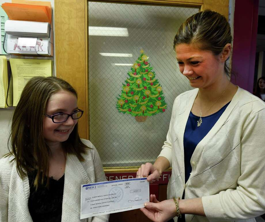 "Emma Zalucky, left hands a check for $525 to Albany Medical Center Foundation representative Kait Ross for Albany Med""s Children's Hospital  after an assembly at the Forest Park Elementary School Monday morning Dec. 22, 2014 in Colonie, N.Y.  Zalucky organized the fundraiser which netted $525 which was over $100 more than last year.   (Skip Dickstein/Times Union) Photo: SKIP DICKSTEIN / 00029886A"