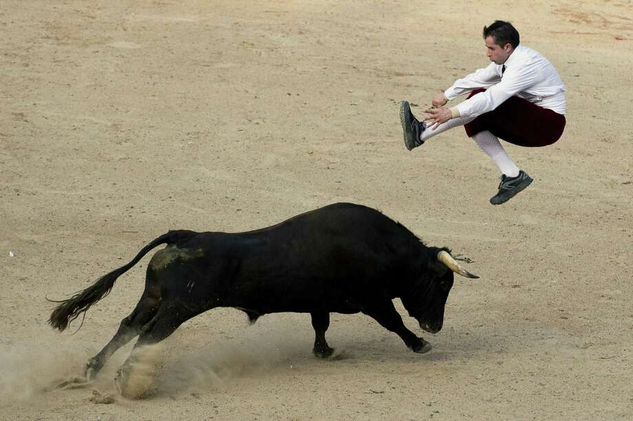 "A man jumps over a bull during a ""recortadores"" bullfight at the Canaveralejo bullring in Cali, Department of Valle del Cauca, Colombia, on December 21, 2014. The recortadores bullfight is an ancient tradition in which men try to dodge the bull without a cape or sword. Bulls are not killed during this type of bullfight. Photo: LUIS ROBAYO, AFP/Getty Images / AFP PHOTO/LUIS ROBAYO"