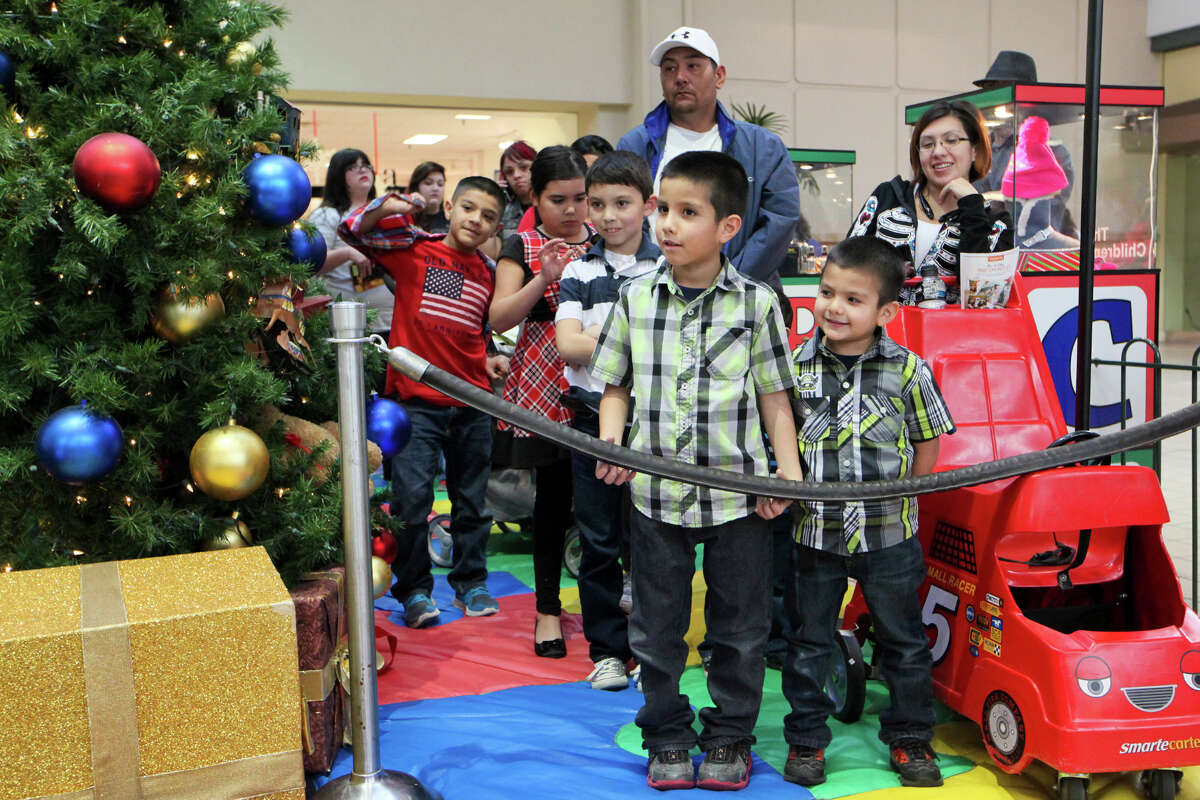 Romeo Carrillo (from right), 5, and Trustin Regalado, 6, wait their turn with others to visit Santa at South Park Mall on Monday, Dec. 22, 2014. MARVIN PFEIFFER/ mpfeiffer@express-news.net