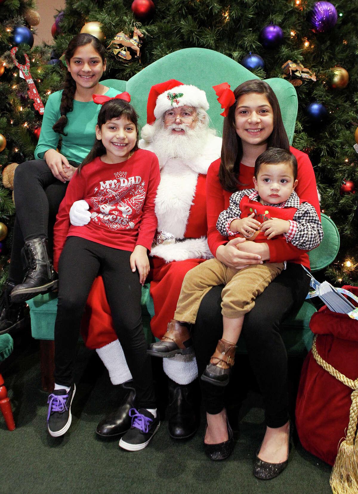 Marisa Berrelez (from left),12, Elisa Berrelez, 9, Ali Berrelez, 13, and Marcus Berrelez, Jr., 1, visit with Santa - aka Duncan Neville - at South Park Mall on Monday, Dec. 22, 2014. MARVIN PFEIFFER/ mpfeiffer@express-news.net
