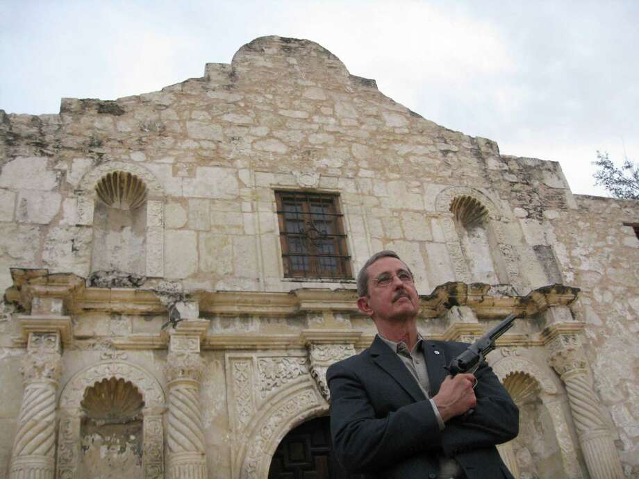 Former Land Commissioner Jerry Patterson poses outside the Alamo on Dec. 22, 2014 with a reproduction of a 1847 Colt Walker, a .44 caliber single-action revolver that remained the most powerful handgun in the world until the 1930s. Patterson, who ran an unsuccessful bid for lieutenant governor in 2014, wants his old job back.  Photo: Sharon Kim / handout