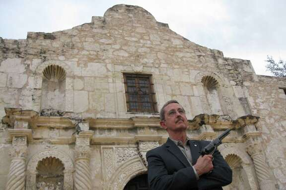 Former Land Commissioner Jerry Patterson poses outside the Alamo on Dec. 22, 2014 with a reproduction of a 1847 Colt Walker, a .44 caliber single-action revolver that remained the most powerful handgun in the world until the 1930s. In Texas, it would have been illegal for anyone who was not a peace officer or other official to carry such a gun under an 1871 prohibition on pistols that is still on the law books today.