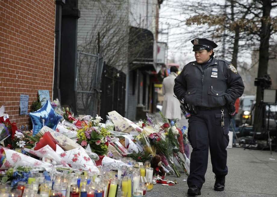 A New York City police officer looks over a makeshift memorial near the site where fellow officers Rafael Ramos and Wenjian Liu were murdered in the Brooklyn borough of New York, Monday, Dec. 22, 2014. Police say Ismaaiyl Brinsley ambushed the two officers in their patrol car in broad daylight Saturday, fatally shooting them before killing himself inside a subway station. (AP Photo/Seth Wenig) ORG XMIT: NYSW108 Photo: Seth Wenig / AP