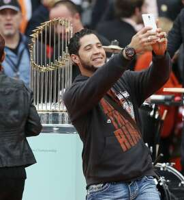 "San Francisco Giants left fielder Gregor Blanco takes a ""selfie"" with the World Series championship trophy during the championship parade ceremony on Friday, October 31, 2014 in the Civic Center of San Francisco, Calif."
