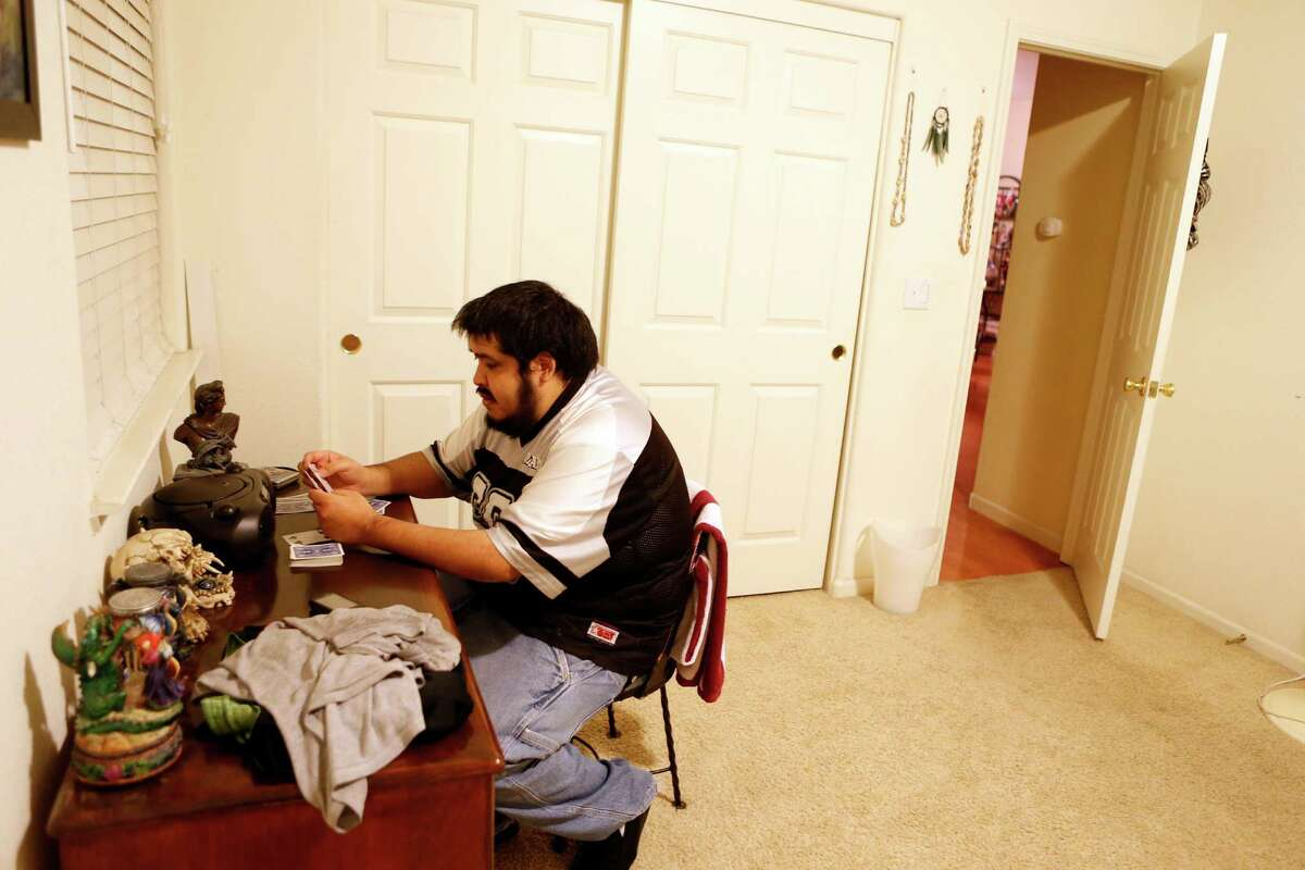 Manuel Cero, who suffers from seizures, plays cards in the bedroom of his home in Brentwood, Calif., on Friday, December 19, 2014.