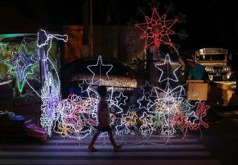 A Filipino Boy Walks Past Christmas Decorations For Sale