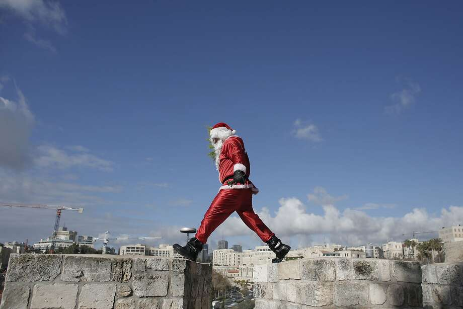 Along the wall of Jerusalem's Old City, a Palestinian dressed as Santa Claus distributes Christmas trees. Photo: Ahmad Gharabli, AFP/Getty Images